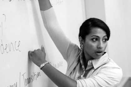 Image of professor pointing to instruction on a whiteboard.