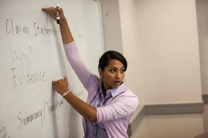 Photo of a professor pointing to writing on a whiteboard.