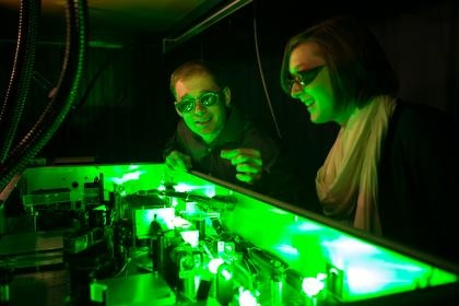 Chemistry students analyzing samples under green light.