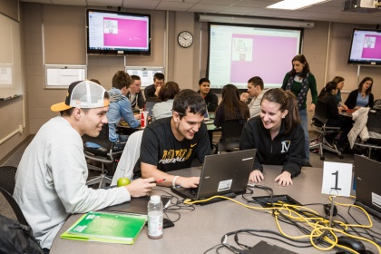 Image of students working on laptops in groups.