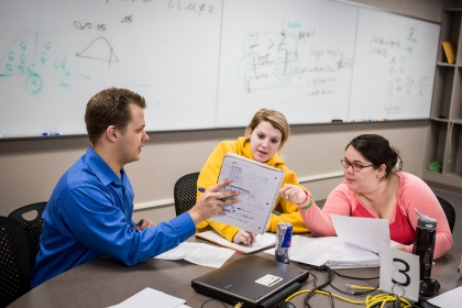 Image of students and professor discussing assignments.