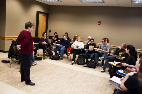 Image of standing professor lecturing to students in a circle.