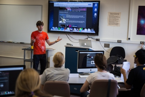 Image of teacher presenting in front of a large computer screen.